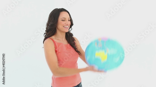 A woman holds a globe in her hand