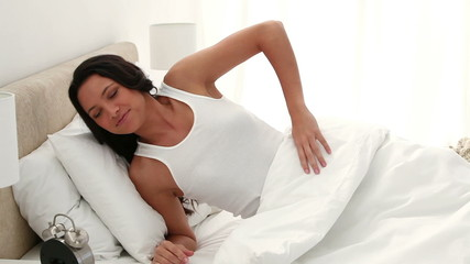 Woman turning off her alarm and stretches