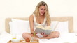 Blonde haired woman having her breakfast while reading