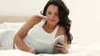 Brunette haired woman reads a book