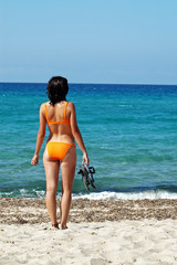 A woman standing in front of the sea in orange bikini and flip-f