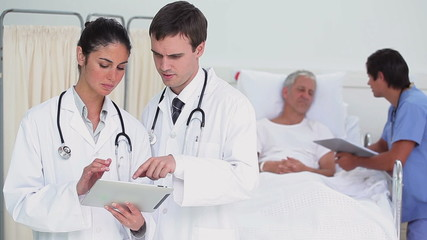 Doctors using a tablet computer