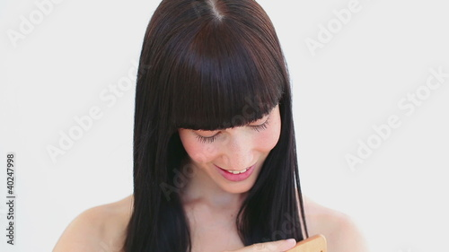 Smiling woman combing her hair
