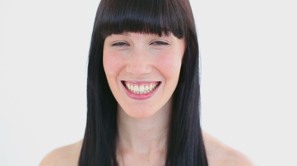 Smiling brunette woman flossing her teeth