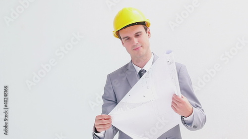 Smiling architect wearing a yellow helmet