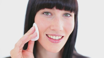 Smiling brunette using a cotton pad
