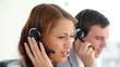 Happy call centre agents talking on their headsets