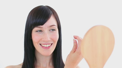 Smiling woman plucking her eyebrow