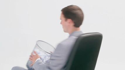 Businessman sitting while holding a wastebasket