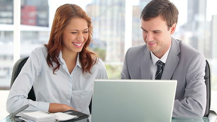 Happy business people using a laptop
