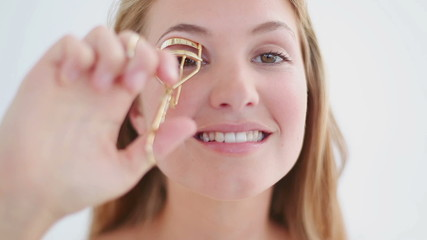 Happy blonde woman using a curler