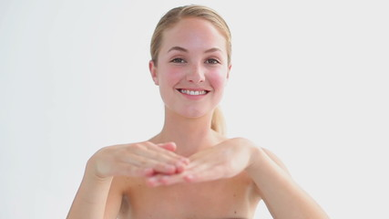 Smiling woman applying moisturizer on her hand