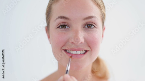 Smiling woman using a lip brush
