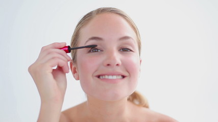 Smiling blonde applying mascara on her eyelashes