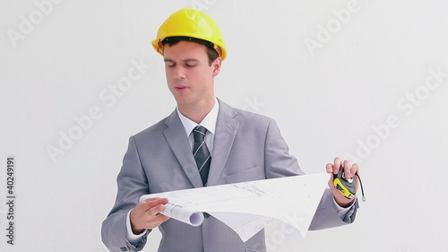 Serious architect reading blueprints