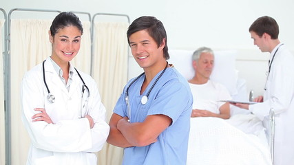 Smiling doctors standing with arms crossed