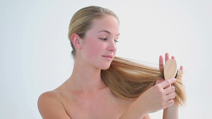 Smiling woman brushing her fair hair