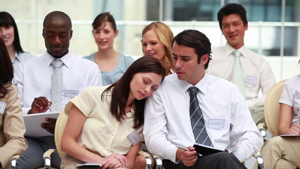 Woman sleeping on her colleagues shoulder