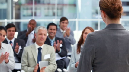Woman being applauded by business people