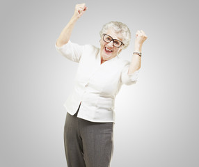 portrait of a cheerful senior woman gesturing victory over grey