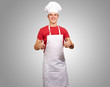 portrait of young cook man doing success symbol over grey backgr