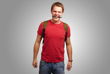 portrait of angry young man biting pen over grey background
