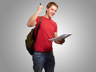 portrait of handsome student holding notebook and pen over grey
