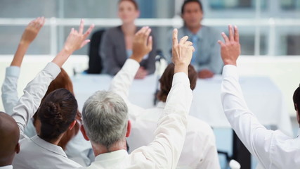 Business people raising their hands to ask questions