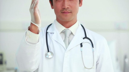 Doctor putting a latex glove on his hand