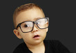 portrait of kid wearing glasses over black background