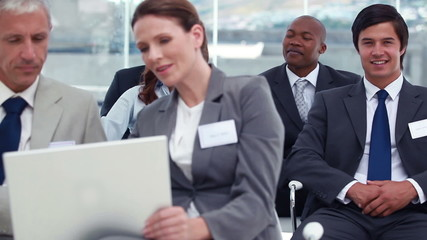 People using a laptop while a businessman looks at camera