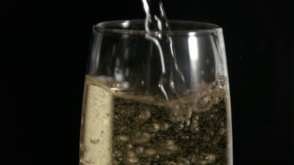 Flute filled in super slow motion with white wine