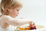 Adorable baby girl eating fresh vegetables