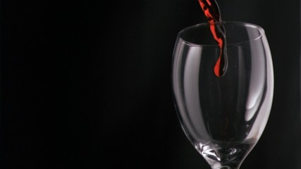 Red wine filling in super slow motion a glass