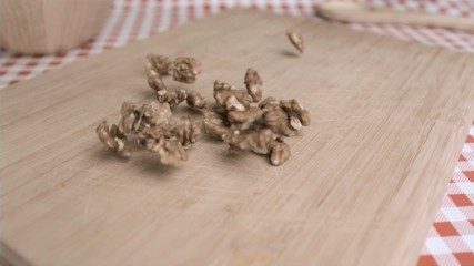 Walnut kernels falling in super slow motion on a wood board