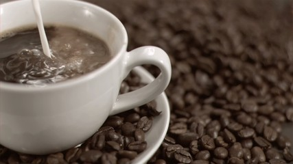 Milk flowing in super slow motion in a coffee cup