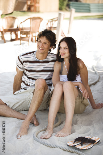 Young couple sitting on sand, smiling