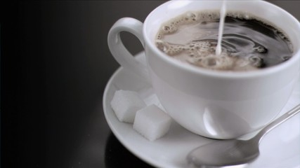 Milk flowing in super slow motion in a cup