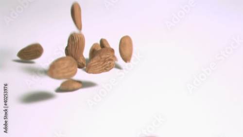 Almonds falling in super slow motion on a white surface