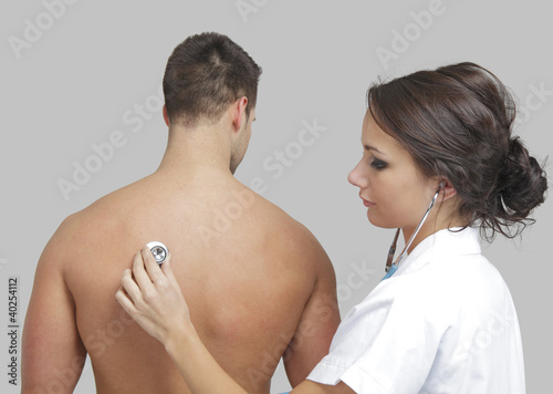 Young female doctor examining a male patient