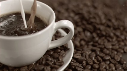Milk poured in super slow motion in coffee