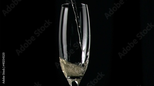 Champagne being poured in super slow motion in glass
