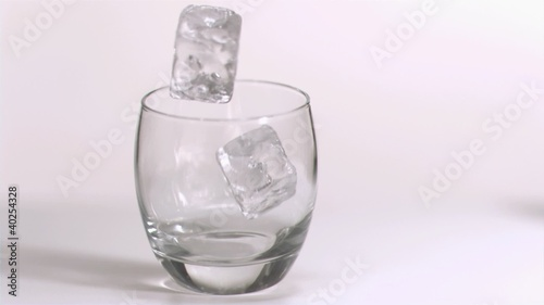Ice cubes rolling in super slow motion in a glass