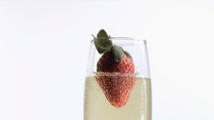 Strawberry diving into champagne in super slow motion