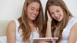 Happy brunette friends looking at a tablet computer