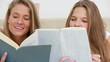 Smiling women reading interesting novels