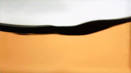 Orange liquid rippling in super slow motion