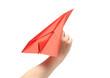 Child's hand launching paper airplane