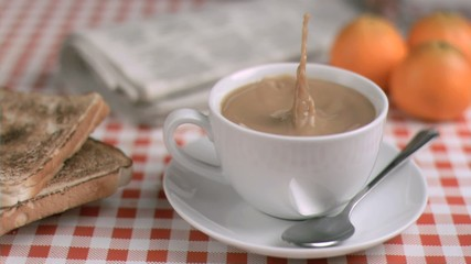 Coffee with milk in super slow motion receiving sugar