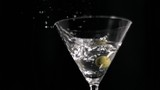 One olive falling in super slow motion in a martini
